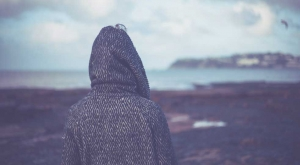 una donna con cappuccio in testa di spalle in riva al mare