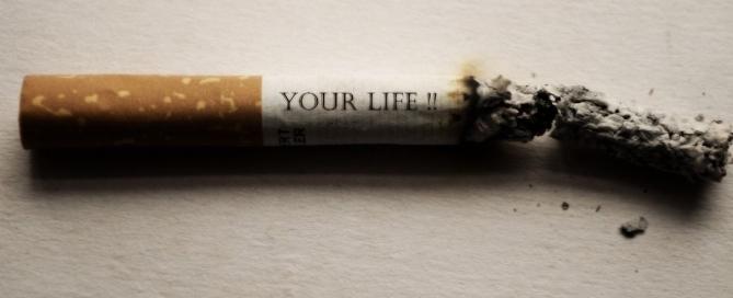 """una sigaretta sta bruciando e reca la scritta """"your life"""" sopra"""