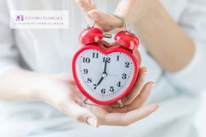 le mani di una donna reggono una sveglia rossa a forma di cuore