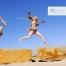 due donne vestite con i costumi dei Neanderthal saltano come in gesto di caccia